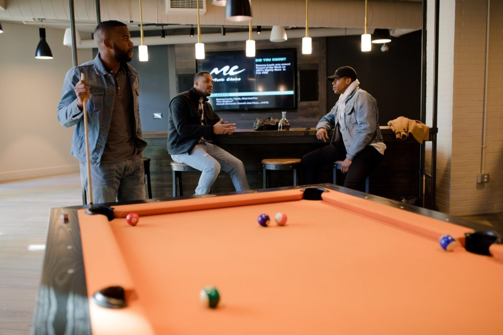 Billiards Table, With Three Men Sitting Around Near a Bar