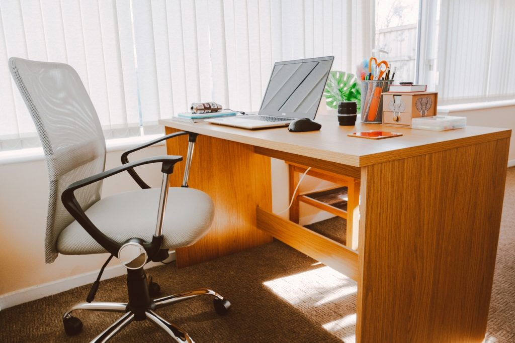 Wooden Office Desk, With a White Rolling Office Chair Nearby